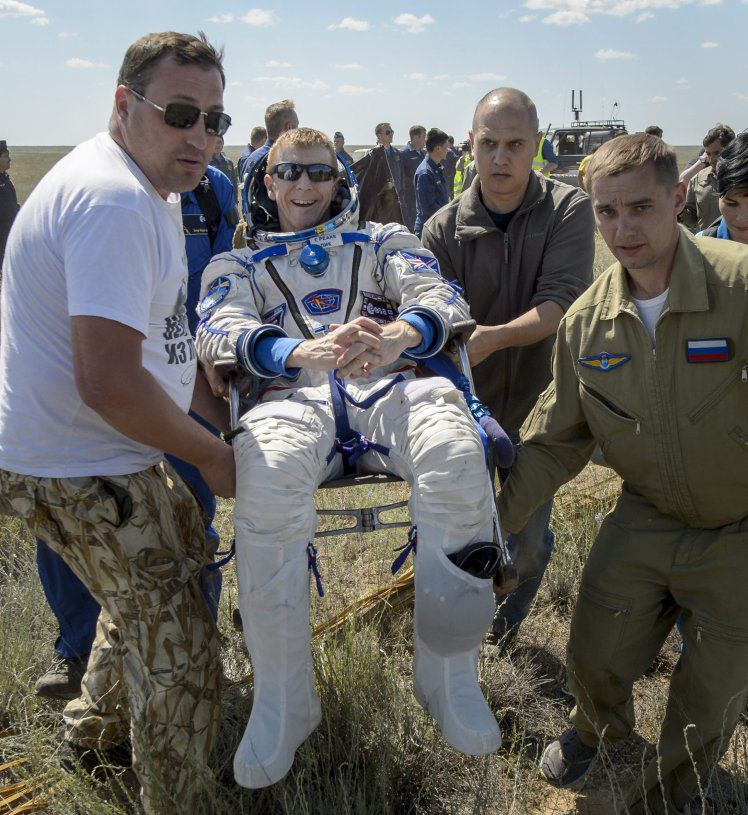 epa05374409 A handout photo provided by the National Aeronautics and Space Administration (NASA) on 18 June 2016 shows Tim Peake (C) of the European Space Agency (ESA) being carried by ground personnel to a medical tent after he along with Yuri Malenchenko of Roscosmos and Tim Kopra of NASA landed in a Soyuz TMA-19M spacecraft in a remote area near the town of Dzhezkazgan (Zhezkazgan), Kazakhstan, 18 June 2016. Kopra, Peake and Malenchenko returned after six months in space where they served as members of the Expedition 46 and 47 crews onboard the International Space Station ISS. EPA/BILL INGALLS/NASA/HANDOUT MANDATORY CREDIT: NASA/BILL INGALLS HANDOUT EDITORIAL USE ONLY