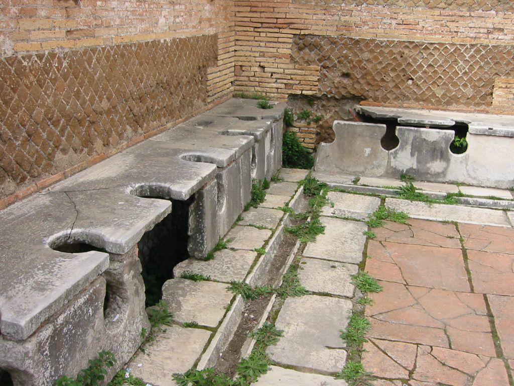 ห้องน้ำโบราณจากสมัยโรมันโบราณ ใน Ostia Antica ซากโบราณสถานที่เป็นเมืองชายฝั่งของอาณาจักรโรมัน, Wikipedia